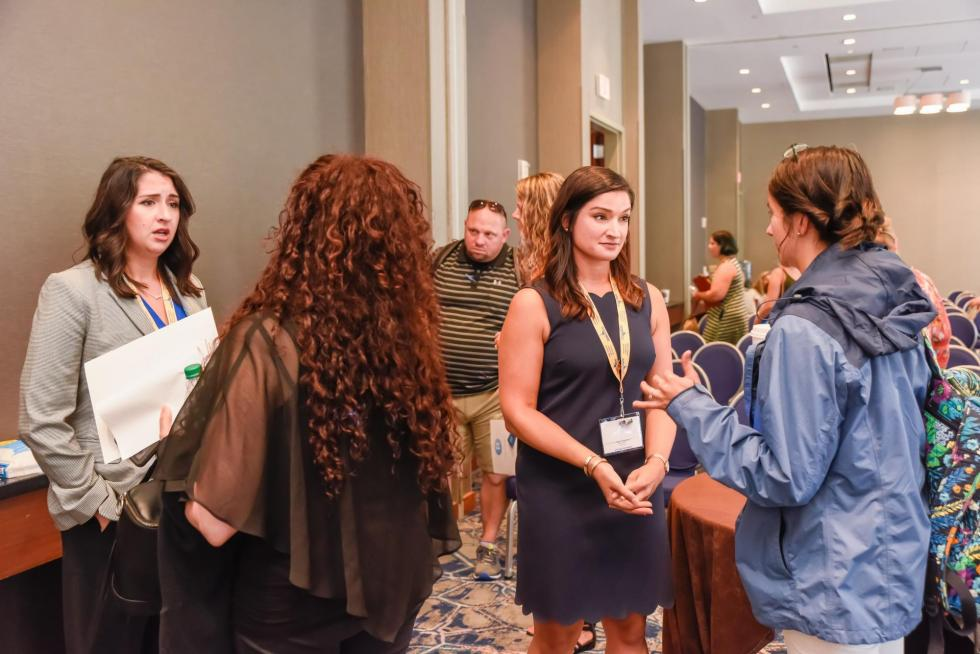 Picture of Kristen Cassidy and Kari Hankins speaking with attendees at the 2019 Making  Schools Work Conference