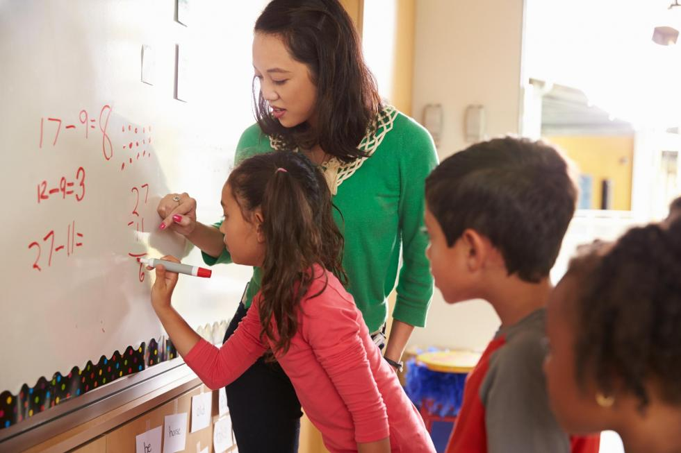 Teacher and elementary school students solve math problems at a whiteboard