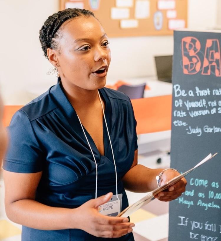 Nija Simmons, an African American college student parent stands holding a paper and presents to her class