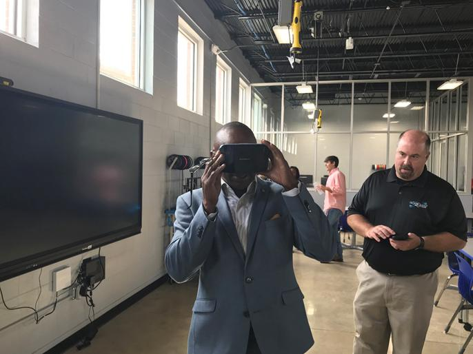 Alabama State Senator Bobby D. Singleton tries out one of Lab 212's virtual reality headsets as Robert Mayben, a trainer with Alabama Technology in Motion, looks on.