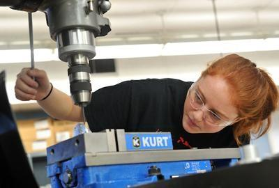Photo of a female CTE student operating a drill press.